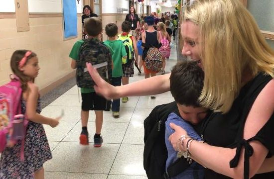 Teacher hugs students